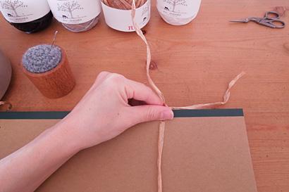 ②糸を1本挟んで、A4ノートに糸を巻きます