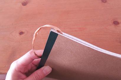 ③糸の端をノートにはさみます