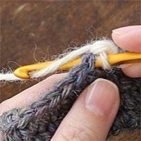 ねじりこま編み[1] 前段の目に針を入れ、糸をかけて引き出します。