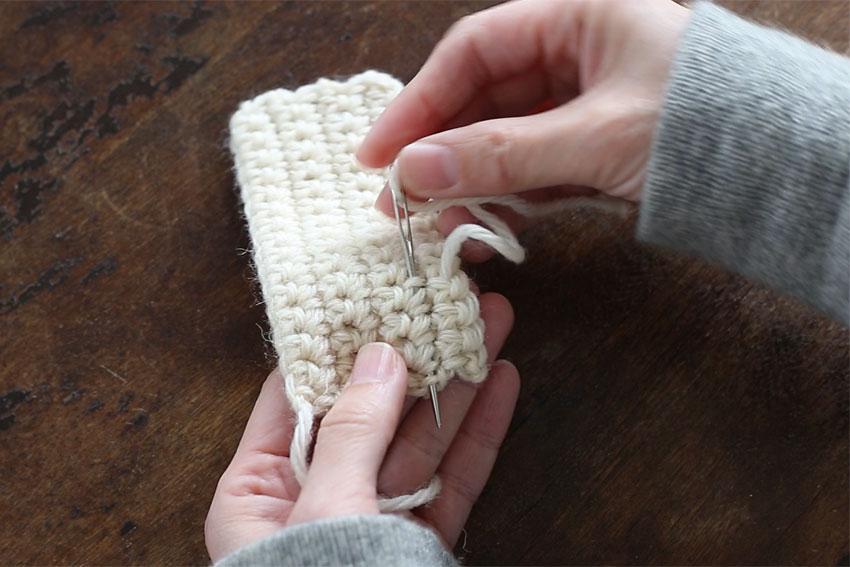 [3] 糸が出ているところからUターンするように、近くの編み地にまた2~3cm針をくぐらせます。