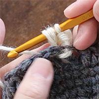 長編み裏引き上げ編み[5] 編み地の裏側に引き出しました。糸をかけ、針先に近い2つのループをくぐらせます。