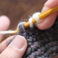 前段の目を束にすくって長編み5目編む[2] 糸をかけ、くさりの下の空間に針を入れました。糸をかけて引き出し、長編みを編みます。