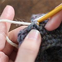 編み地の途中に糸をつける[3] 針に糸をかけて引き出します。