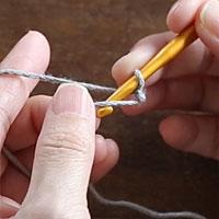 スレッドコードの編み方[4]親指側の糸を、手前から向こうに向かって、針にかけます。
