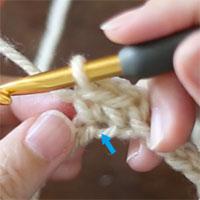 2つ目のこま編みが編めました。こま編みの目の下の矢印のところに、拾わなかった「作り目のくさり」の残りの1本が見えています。